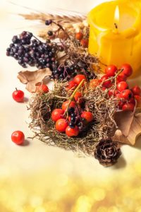 Autumn card with autumn berries and yellow burning candle over bokeh background